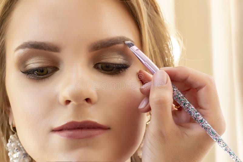 Maskenbildner setzt Make-up auf Mädchenmodell Bürste treffen Lidschatten auf Augenbrauen zu schönes Mädchenmodell, Porträt Nackte stockfotos
