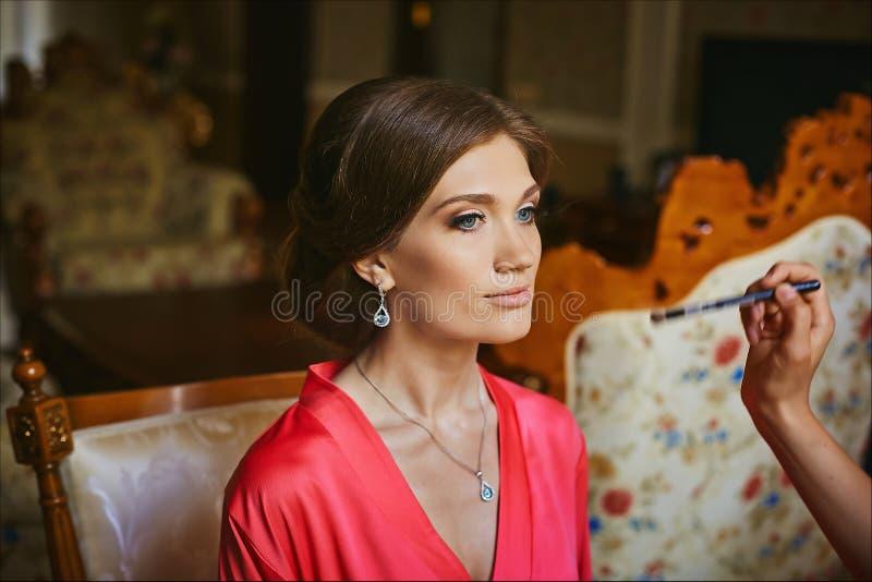 Maskenbildner wendet das Make-up für junge Frau des schönen Brunette mit blauen Augen an und trägt in Pfirsich peignoir - Braut ` lizenzfreies stockbild