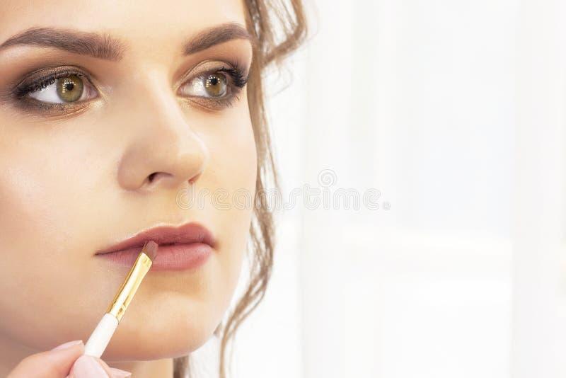 Maskenbildner wendet Make-up am Modell an Lippenpinsel für Lippenstift schönes Mädchenmodell, Porträt Nackte Farben im Make-up Wi lizenzfreies stockbild