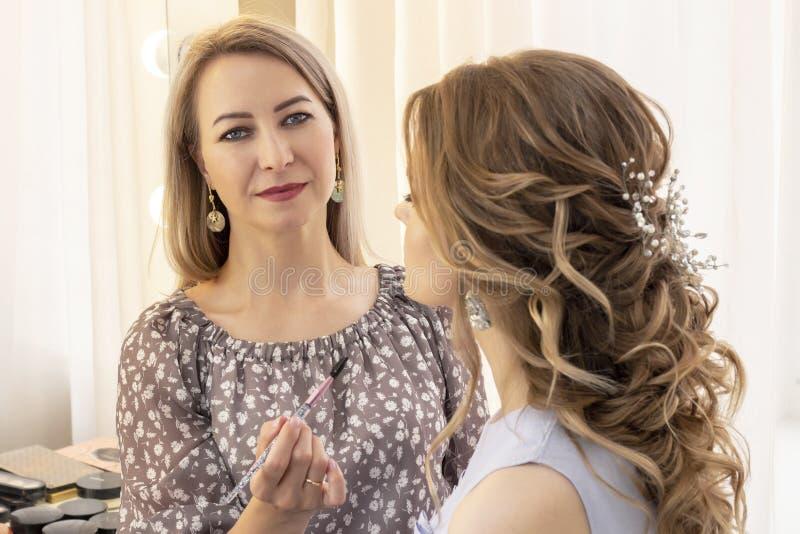 Maskenbildner wendet Make-up am Modell an Lippenpinsel für Lippenstift schönes Mädchenmodell, Porträt Nackte Farben im Make-up Wi stockfoto