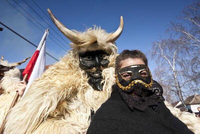 Masker di carnevale in pelliccia con una ragazza 'di Sokac' 'al Busojaras', il carnevale del funerale dell'inverno fotografia stock