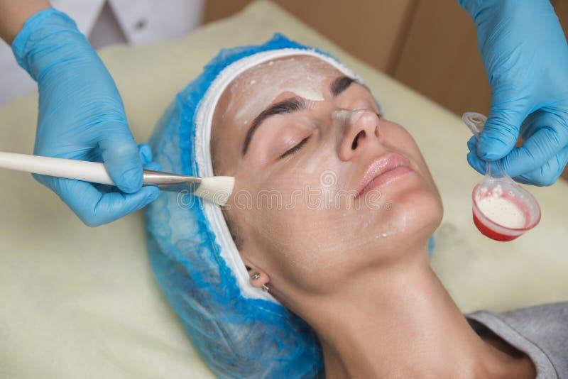 Masker voor het gezicht De vrouw in een schoonheidssalon maakt een masker stock afbeelding