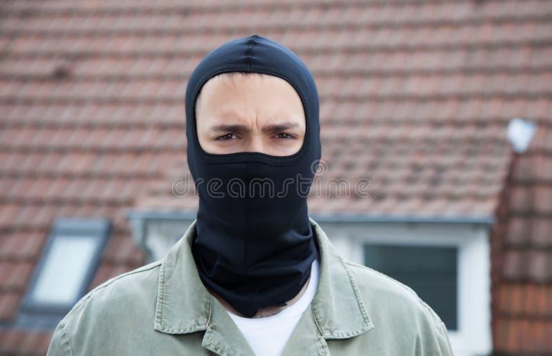 Maskerad inbrottstjuv med tak i bakgrunden royaltyfri fotografi