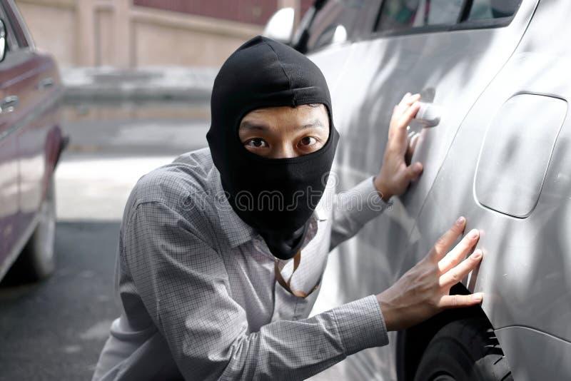 Maskerad inbrottstjuv som bär en balaclava som är klar till inbrottet mot bilbakgrund Försäkringbrottbegrepp royaltyfri fotografi
