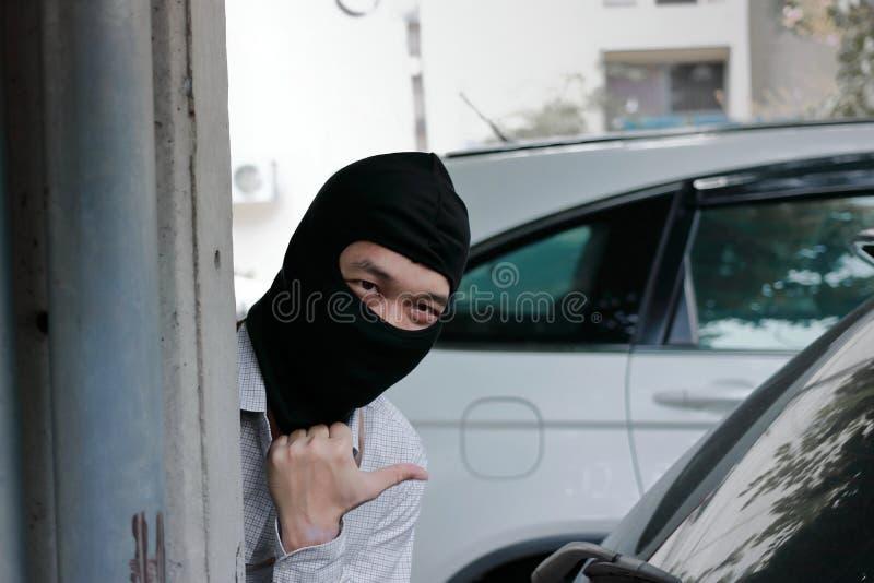 Maskerad inbrottstjuv som bär en balaclava som är klar till inbrottet mot bilbakgrund Försäkringbrottbegrepp fotografering för bildbyråer