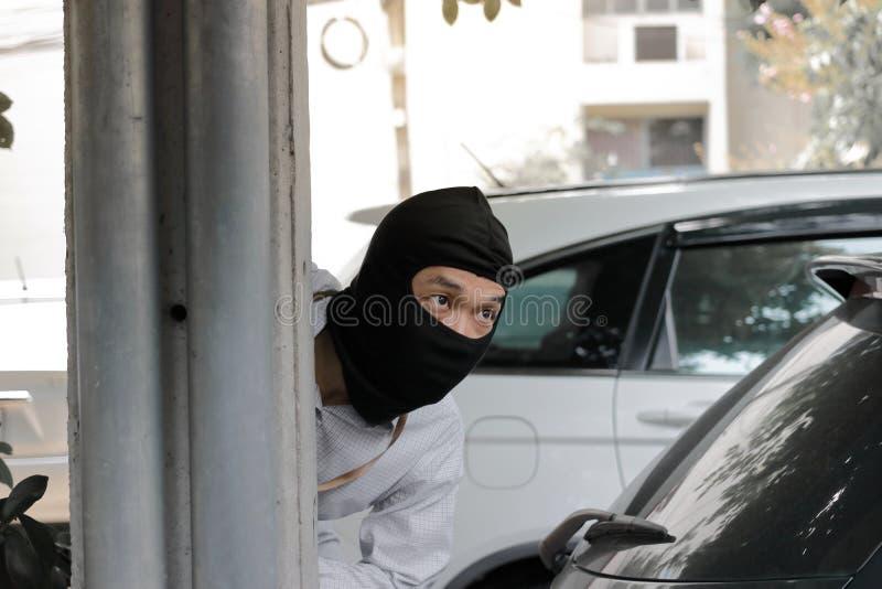 Maskerad inbrottstjuv som bär en balaclava som är klar till inbrottet mot bilbakgrund Försäkringbrottbegrepp arkivbilder
