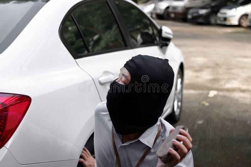 Maskerad inbrottstjuv som bär en balaclava som rymmer den lilla stenen klar till inbrottet mot bilbakgrund Försäkringbrottbegrepp royaltyfria bilder