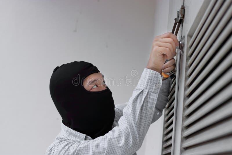 Maskerad rånare som använder ett låsplockninghjälpmedel till avbrott och att skriva in in i ett hus Brottsligt brotts- begrepp arkivfoto