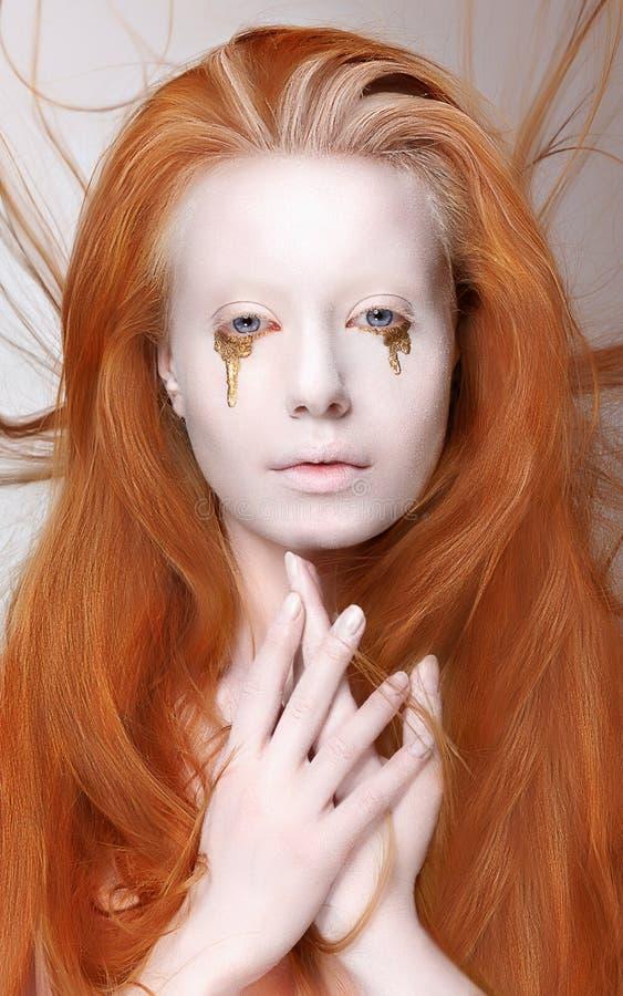 Maskerad. Rödhårig mankvinna med futuristiskt smink. Fantasi fotografering för bildbyråer