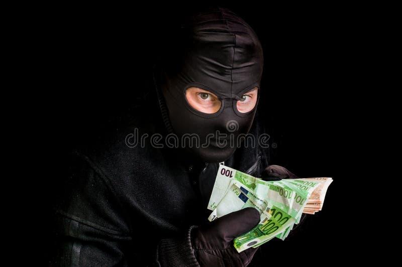 Maskerad tjuv i balaclava med stal pengar som isoleras på svart arkivbild
