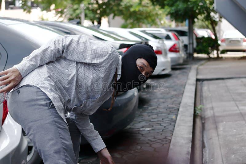 Maskerad tjuv i den svarta balaclavaen som försöker att bryta in i bilen arkivbilder