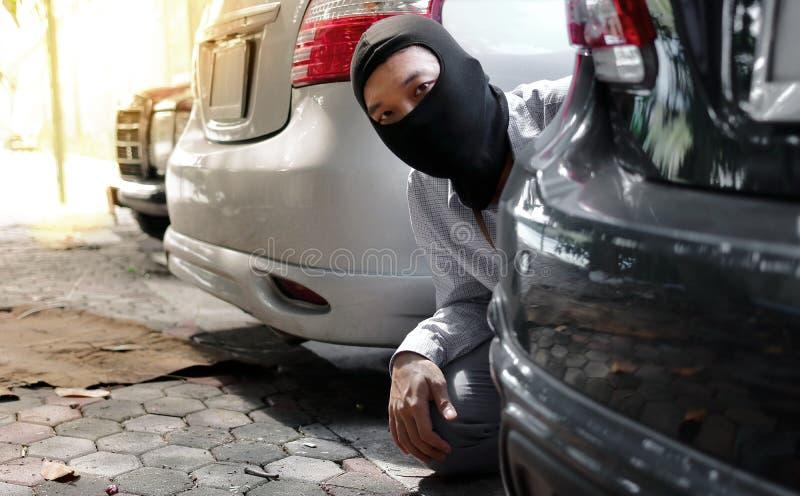 Maskerad tjuv i den svarta balaclavaen som försöker att bryta in i bilen Brottsligt brotts- begrepp royaltyfria bilder