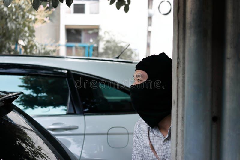 Maskerad tjuv i den svarta balaclavaen som försöker att bryta in i bilen Brottsligt brotts- begrepp royaltyfri foto