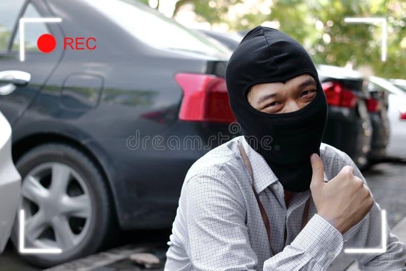 Maskerad tjuv i den svarta balaclavaen som försöker att bryta in i bilen med skärm för cctv-kamerasökare Brottsligt brotts- begre arkivbild