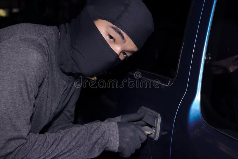 Maskerad tjuv med balaclavaen med tangent till avbrott in i en bil vägg för skugga för pistol för holding för brotts- främre hand arkivfoto