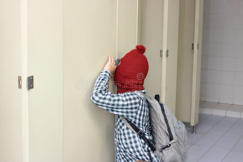 Maskerad tjuv med en balaclava som smyga sig i toalett Socialt riskbegrepp arkivfoton