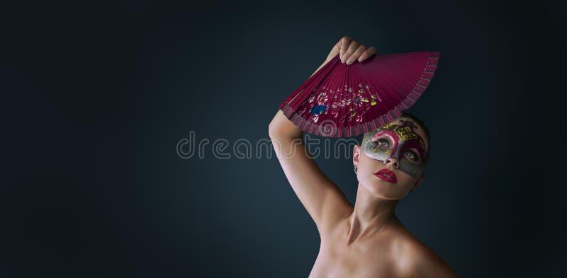 Maskerade-Karnevalsmaske der Frau tragende venetianische stockfoto