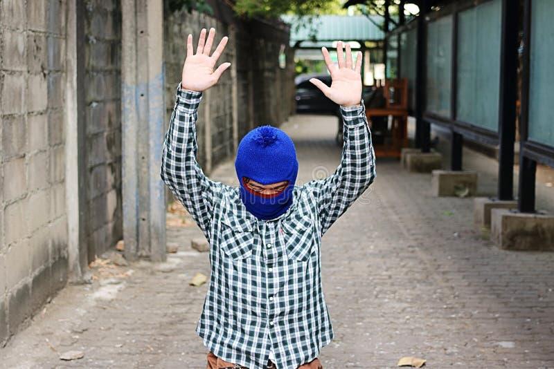 Maskerade tjuvstopp och lyftahänder upp Låsinbrottstjuvbegrepp royaltyfri foto