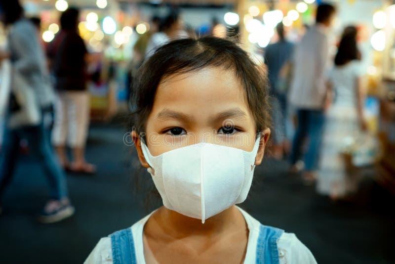 Maskering för skydd för gullig asiatisk barnflicka bärande till mot luftsmogförorening med e.m. 2 5 royaltyfria bilder