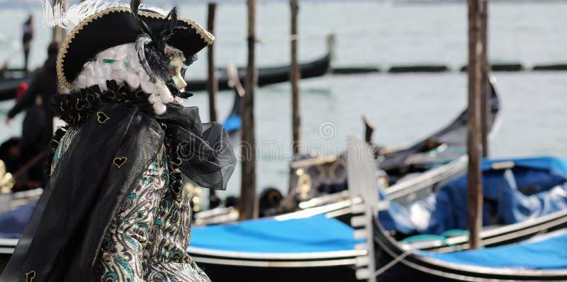 maskering och gondoler i ön av Venedig under karnevalet royaltyfri fotografi