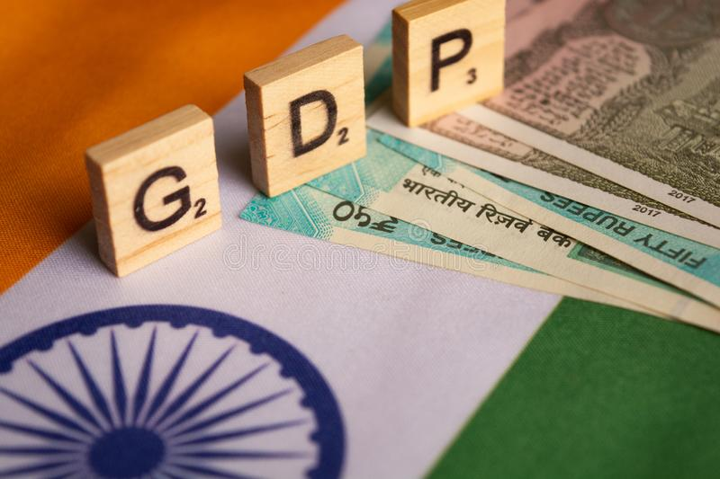 Maski,India 13,April 2019 : GDP or gross domestic product in wooden block letters on Indina flag with Indian Currency royalty free stock images