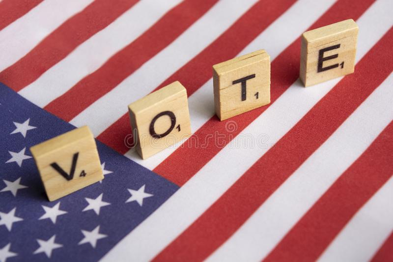 Maski, India 26, April 2019 : Vote wooden block letters on US flag royalty free stock photography