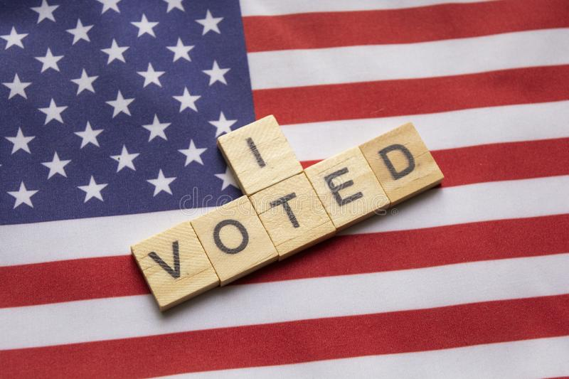 Maski, India 26, aprile 2019: Ho votato i caratteri in grassetto di legno, elezioni degli Stati Uniti sulla bandiera americana fotografie stock libere da diritti