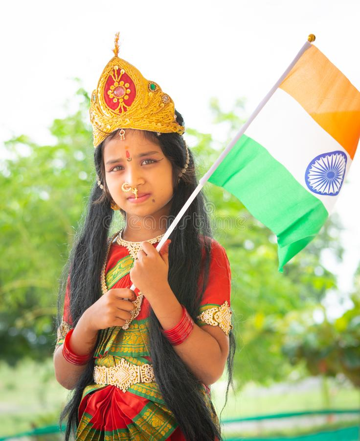 Maski, India August 15, 2019 : Small cute little Indian Girl kid in Bharat mata or Mother India attire with Indian Flag in hand.  stock photos