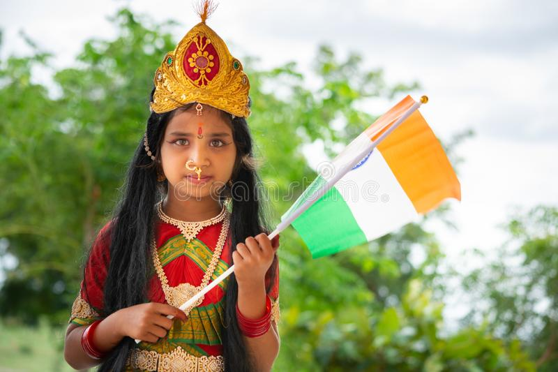 Maski, India August 15, 2019 : Small cute little Indian Girl kid in Bharat mata or Mother India attire with Indian Flag in hand.  stock photography
