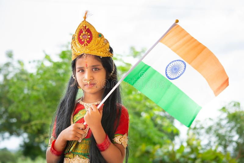 Maski, India August 15, 2019 : Small cute little Indian Girl kid in Bharat mata or Mother India attire with Indian Flag in hand.  stock photo