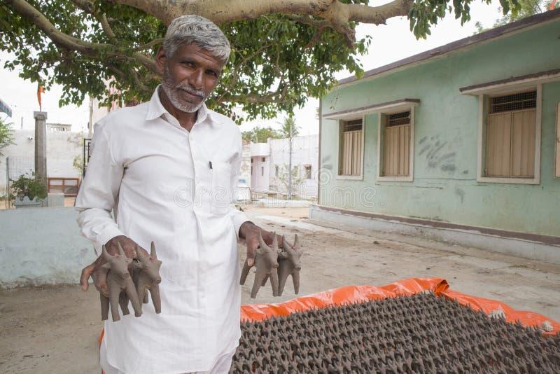 Maski, India 01 Juli, 2019: De oude die mens het verkopen Ossen maakten met modderklei, tijdens het festival bij het begin van de stock foto