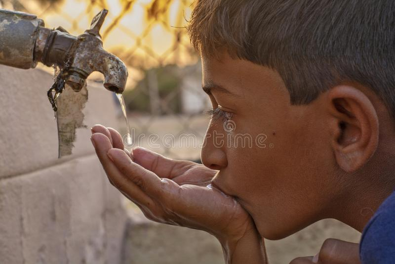Maski, Karnataka, Индия - 26, март 2019: Крупный план питьевой воды ребенка сразу от воды из крана корпорации в Индии стоковые фотографии rf