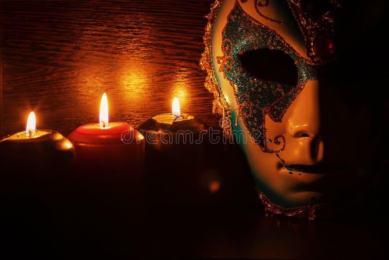 Maskieren Sie Maske und Kerzen auf einem schwarzen Hintergrund stockfotografie