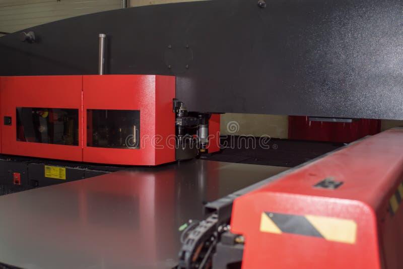 Maskin för att stansa hål i metall på fabriken arkivbilder