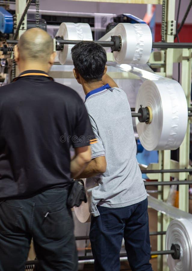 Maskin för extruder för arbetarreparationsplastpåse royaltyfria bilder