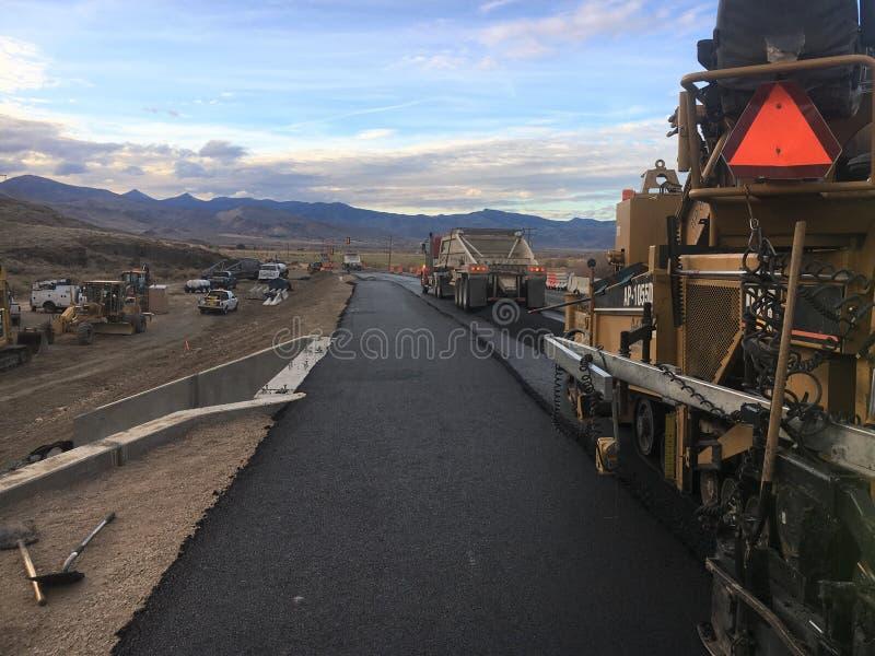 Maskin för stenläggning för vägkonstruktion med lastbilen som levererar asfalt arkivbilder