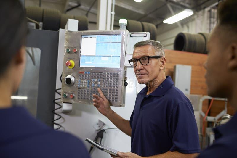 Maskin för teknikerTraining Apprentices On CNC arkivfoto