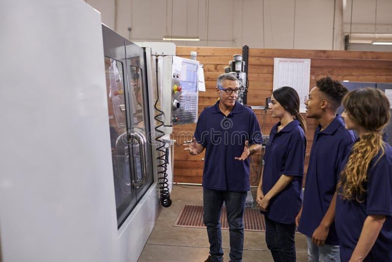 Maskin för teknikerTraining Apprentices On CNC royaltyfri foto