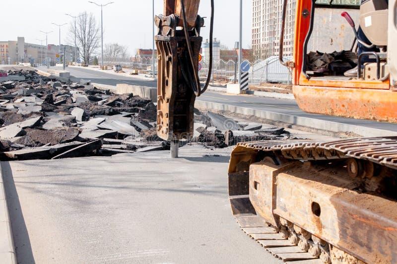maskinen borrar asfalt Stora fragment av land och gropar ?verallt p? v?gen arbetande utrustning med arbeten f?r en drillborr h?gt royaltyfri bild