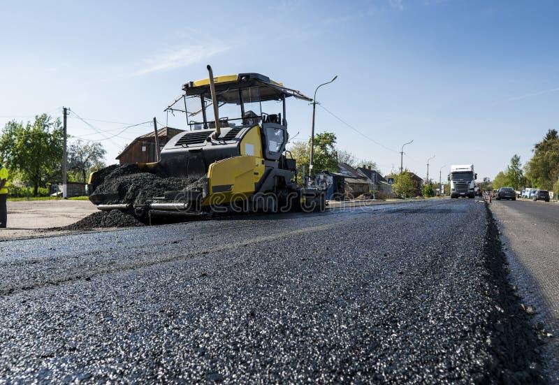 Maskinen för paveren för arbetarfungeringsasfalt under konstruktion och att reparera för väg fungerar En paverefterbehandlare, as royaltyfria bilder