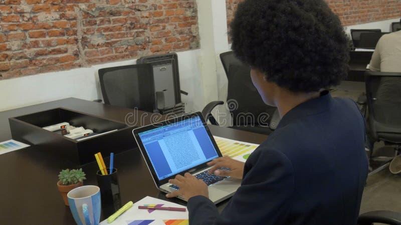 Maskinskrivning för afrikansk amerikanaffärskvinna genom att använda businesspeople för bärbar datordator stock video