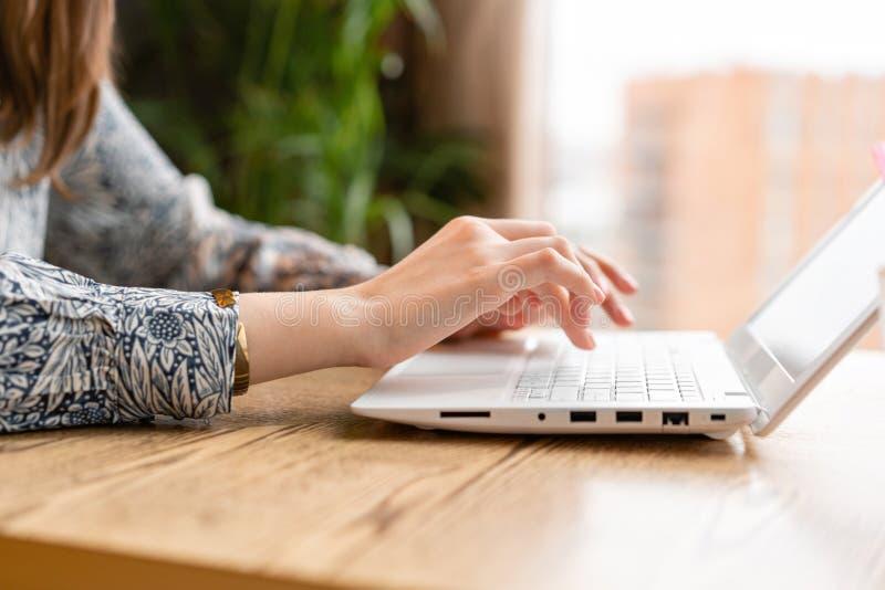 Maskinskrivning för den unga kvinnan på tangentbordet som pratar, underhåller en blogg Freelancerarbete i modern coworking lyckat royaltyfri bild