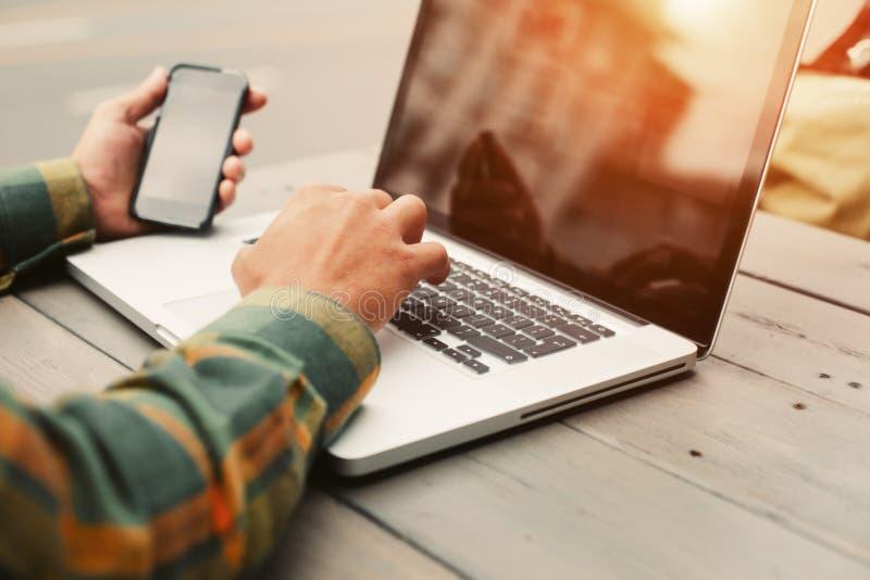 Maskinskrivning för ung man på datoren och sammanträde i gatakafét, freelancer som utomhus gör hans jobb royaltyfri foto