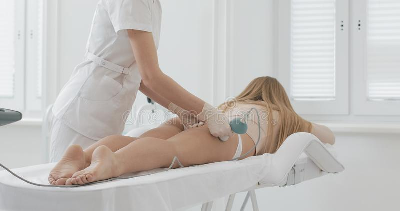 Maskinvarudiagram korrigering UltraljudCavitationkropp som drar upp konturerna av behandling Härlig kvinna som får anti--cellulit arkivbilder