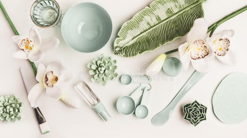 Maskowy muśnięcie, puchar, szpachelka, pomiarowe łyżki i kwiaty na białym desktop tle, odgórny widok obraz stock