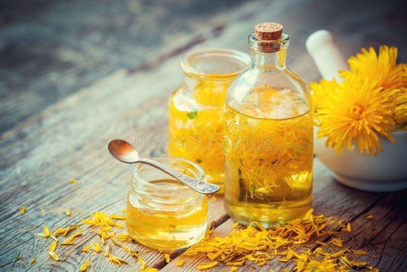 Maskrostinktur eller olje- flaskor, mortel och honung på tabellen royaltyfria bilder