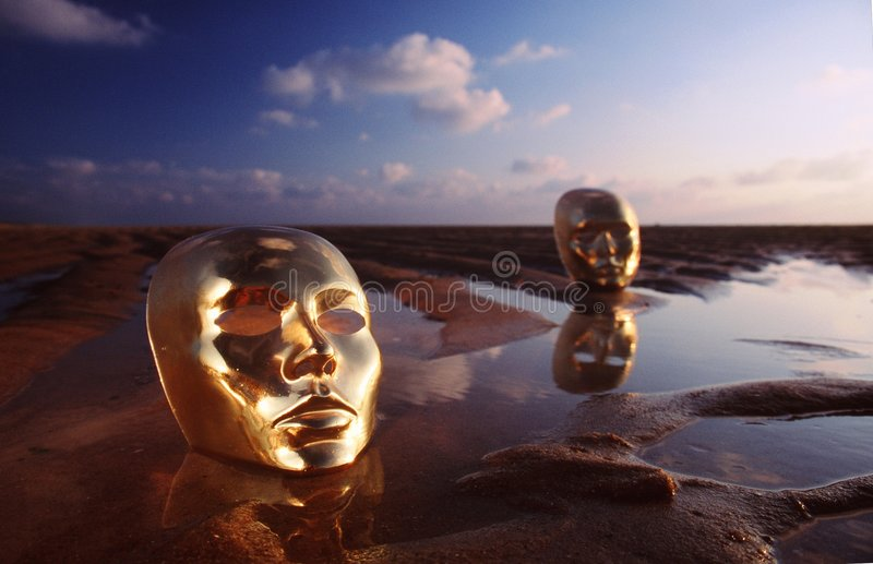 Masks on water. Reflecting masks on the beach royalty free stock photo