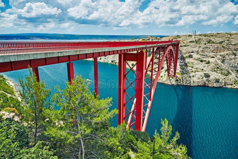 maslenica γεφυρών maslenica γεφυρών Μια κόκκινη γέφυρα που συνδέει δύο τράπεζες Άσπρα σύννεφα στον ουρανό και την μπλε θάλασσα στοκ εικόνες με δικαίωμα ελεύθερης χρήσης