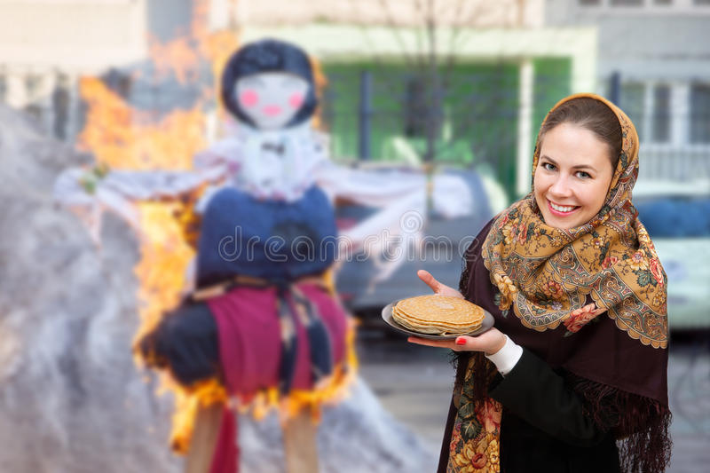 Maslenitsa燃烧的钝汉的一个微笑的少妇  免版税库存图片