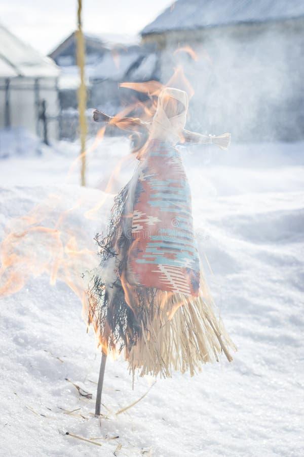 Maslenitsa in Rusland De kleine pop is een symbool van Maslenitsa, brandt de vogelverschrikker als symbool van het eind van stock afbeeldingen